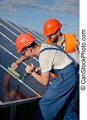 Technicians installing photovoltaic panels at solar power...
