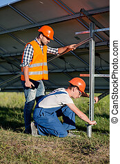 Builders installing frame with solar panels on helical pile....