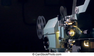 Traditional mechanical movie projector in operation. -...