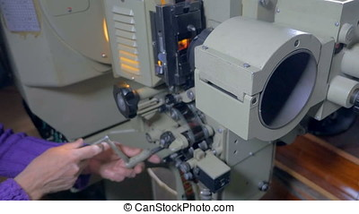 Big film projector being turned on. - Large old-fashioned...