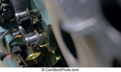 Tape going through opto-mechanical film projector. -...