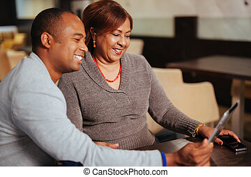 A mother and son hold a computer tablet, isolated - A mother...