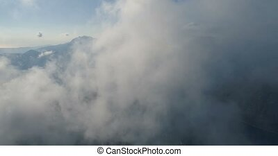 flying above the clouds, aerial view of mountains clouds and...