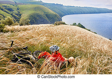 The attractive cyclist sitting on the grass on the meadow...
