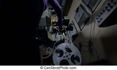 Woman turning on old film projector. - Old-fashioned optical...