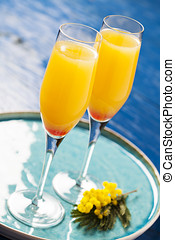 Two glasses with mimosa cocktail (sparkling wine plus orange...