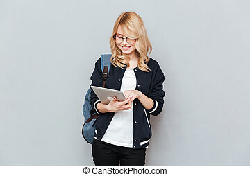 Woman with tablet - Smiling woman student wearing glasses...