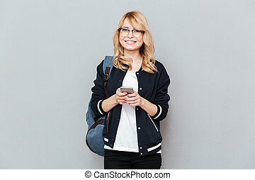 Student with phone looking camera - Smiling student wearing...