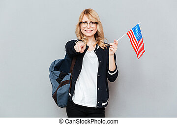 Student with flag - Smiling female student holding flag and...