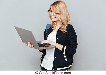 Student using laptop - Smiling student in glasses and with...