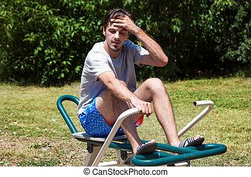 tired young man after exercise outdoor on rowing machine -...