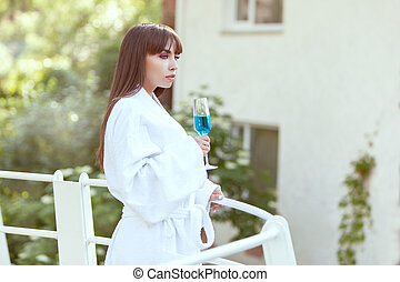 Woman on the balcony with wine. - Woman is on the balcony of...
