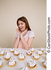 Happy young lady sitting and posing near cupcakes - Photo of...