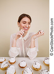 Happy young lady posing while eating cupcakes. - Image of...