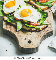 Bread toasts with fried eggs and fresh vegetables, square...