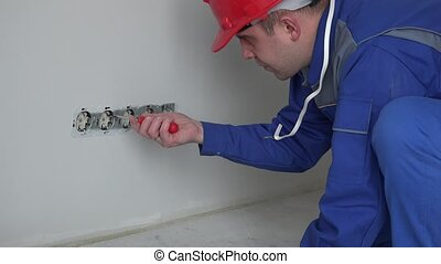 Electrician man with screwdriver installing socket outlet...