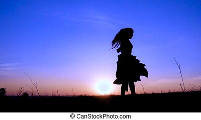 Silhouette of young witch dancing at field against blue...
