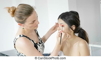 Slow motion. Makeup artist applying makeup products with...
