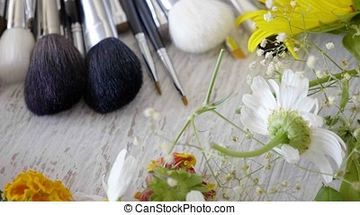 Make-up brushes laying on wooden table next to flowers