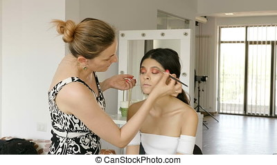 Makeup artist applying makeup products with brushes on a...