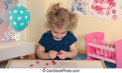 lovely girl child unwrap sweets candies from paper and taste...