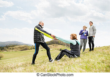 Group of active senior runners outdoors, resting. - Group of...