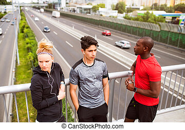 Young runners in the city resting on a bridge.