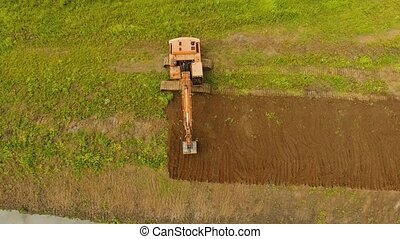 Excavator digging a trench in the field.Aerial video. -...