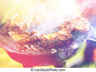 meat cooking on barbecue grill at summer party - food and...