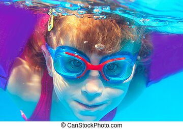 Underwater swimming girl goggles blue water portrait