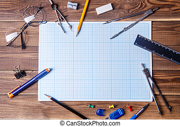Graph paper with copyspace and student material on wooden table.