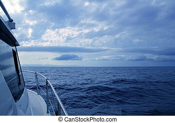 Boat sailing in cloudy stormy day blue ocean sea, yacht side...