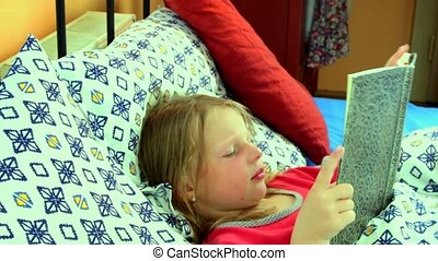 Little girl in bed. Girl looks at an old father diary. Small...