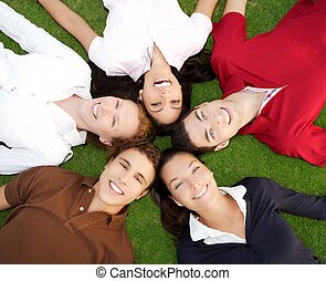 friends happy group in circle together on grass - friends...