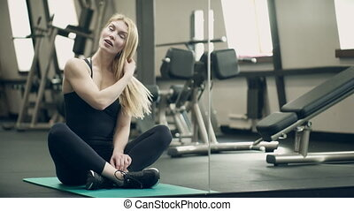 In the gym, a beautiful woman sits in a lotus position and...