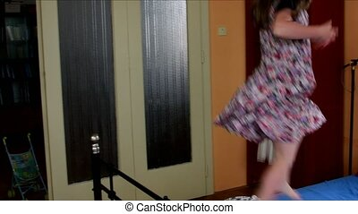 Cute little girl dances on a bed. Childhood concept