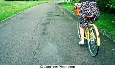 Unknown young woman riding her bicycle along park bike path