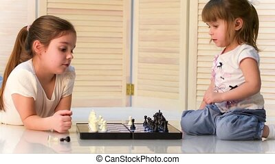 Children playing chess - Two girls play at home, laughing...