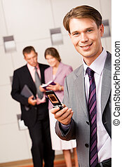 Dialing - Portrait of successful manager dialing on the...