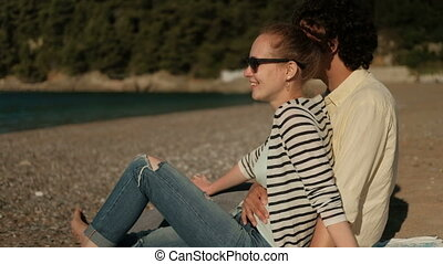 A loving couple is sitting on a sunny beach and flirting.
