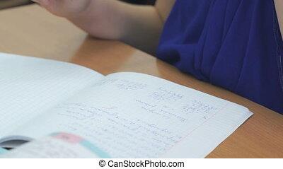 Schoolgirl writes in notebook with ballpoint pen - The...