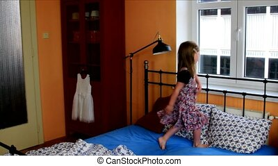 Cute little girl dances on a bed. SLow motion. Childhood concept
