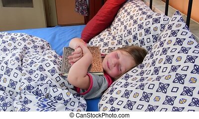 Little girl in bed. Girl tryies get asleep with an old father diary. Small girl with an old book in bed. Family concept