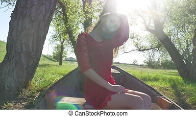 girl sitting in the old boat. young woman in a red dress...