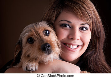 Woman and Her Pet Dog - A young woman in her 20s holds a...