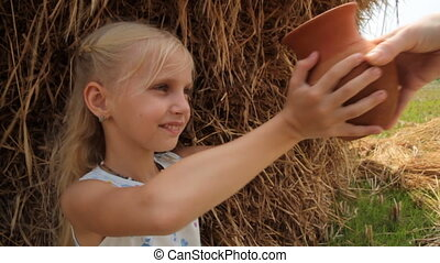 Pretty girl drinks fresh cows milk from a clay pot against the backdrop of a haystack on a farm.