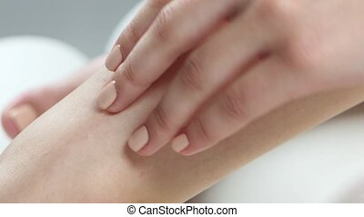 Girl spends her hand over her smooth skin on her leg. Close...