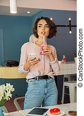 Young pretty girl holding mobile phone and drinking smoothie...
