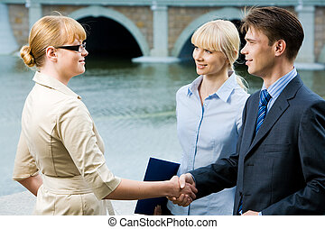 Agreement - Portrait of business partners handshaking at...