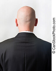 Back of man - Rear view of bald man wearing suit over white...
